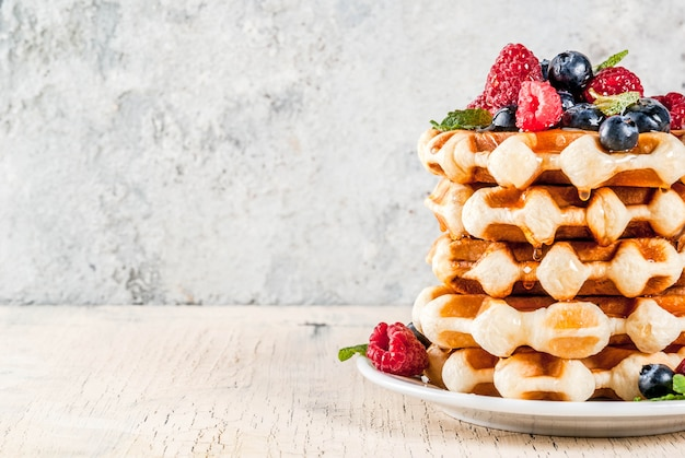 Belgian waffles with raspberries, blueberries and syrup, homemade healthy breakfast, light concrete background copy space