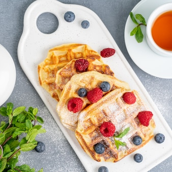 Belgian waffles with raspberries, blueberries, tea, top view. healthy homemade breakfast