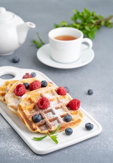 Belgian waffles with raspberries, blueberries, tea, vertical. healthy homemade breakfast