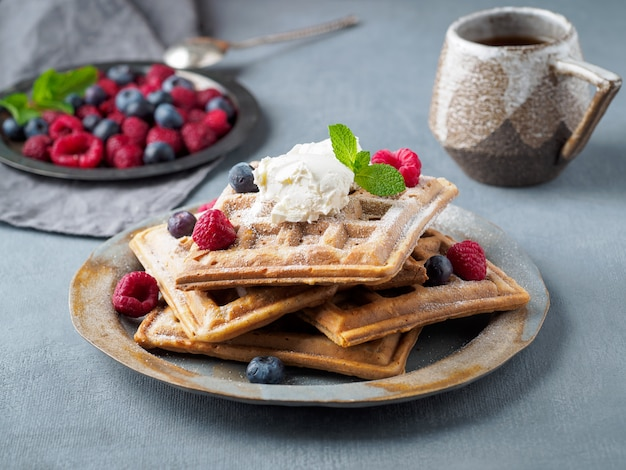 Belgian waffles with raspberries, chocolate syrup. breakfast with tea on dark background, side view