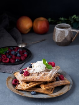 Belgian waffles with raspberries, chocolate syrup. breakfast with tea on dark background,  vertical