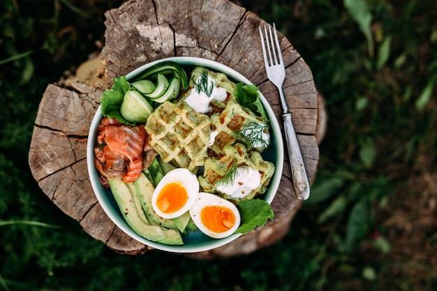 접시에 연어 아보카도와 계란을 넣은 벨기에 와플