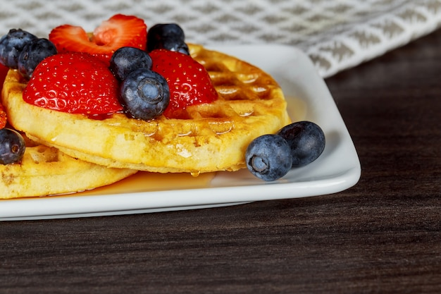 Belgian waffles with strawberries, blueberries and syrup, homemade healthy breakfast