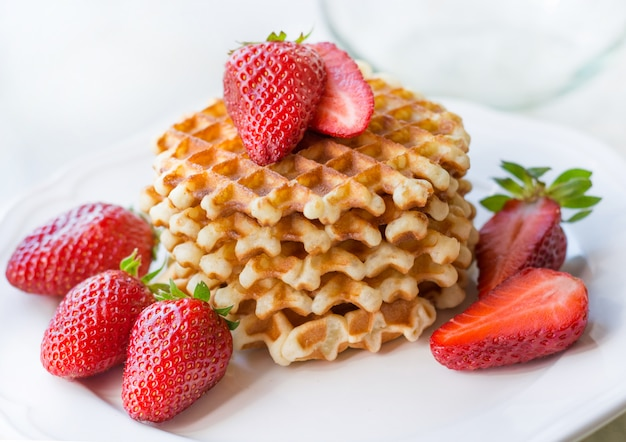 Belgian waffles with strawbery on white plate.