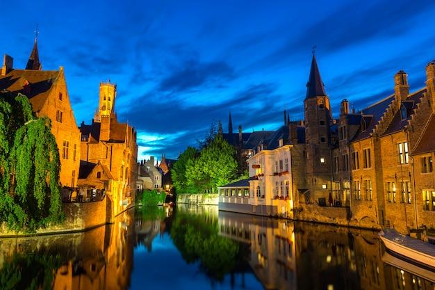 ベルギー、ブルージュ、川、夜景、ガラスの水面に石造りの建物がある古代ヨーロッパの町。