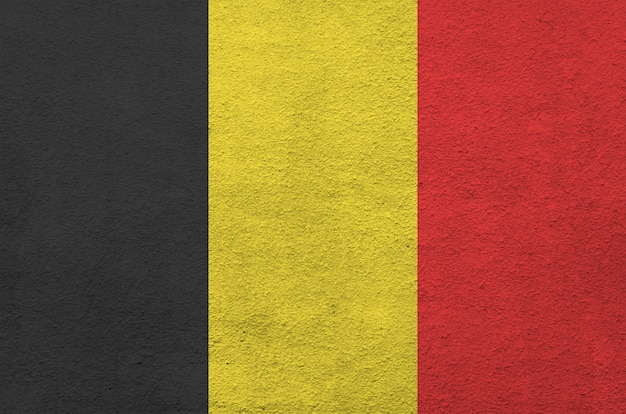 Belgium flag depicted in bright paint colors on old relief plastering wall. textured banner on rough background
