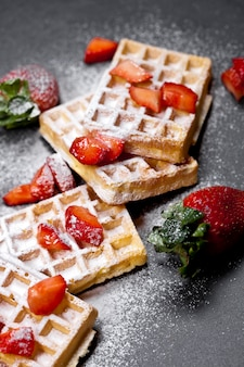Belgium waffers with strawberries and sugar powder on black board.