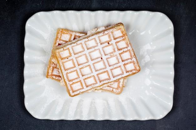 Belgium waffers with sugar powder on ceramic plateon black board background.