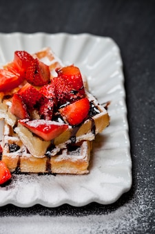 Belgium waffers with sugar powder, strawberries and chocolate on ceramic plate on black board.