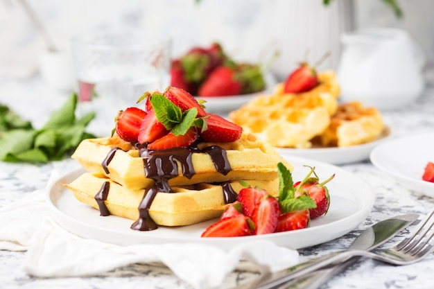 Belgium waffles with chocolate topping and strawberries. breakfast food