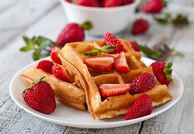 Belgium waffles with strawberries and mint  on white plate Free Photo