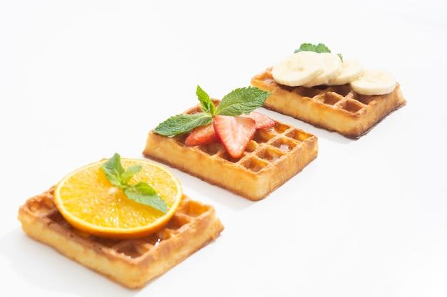 흰색에 시럽을 얹은 딸기 바나나와 오렌지를 곁들인 벨기에 와플
