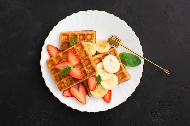 검은 돌 배경에 접시에 딸기, 바나나, 민트, 꿀 벨기에 와플