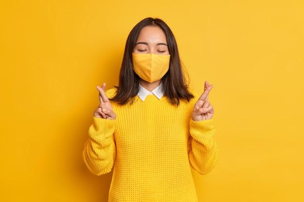 すべてをより良く信じる。アジアの女性は顔に保護マスクを着用し、指を交差させ、コロナウイルスがなくなることを願って、パンデミックの発生時に身を守ります。