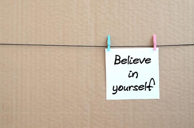 Верь в себя. примечание написано на белой наклейке, которая висит