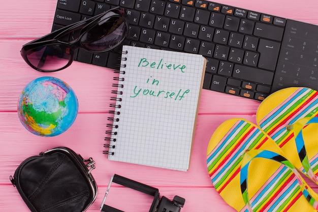 ピンクのテーブルトップの背景に女性の旅行者アクセサリーメガネ財布と黄色のビーチサンダルでノートブックを信じてください。グローブと黒のキーボード。