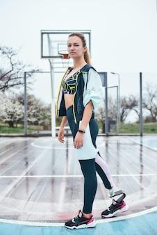 Поверьте в себя, молодая и сильная женщина-инвалид в спортивной одежде стоит на стадионе и