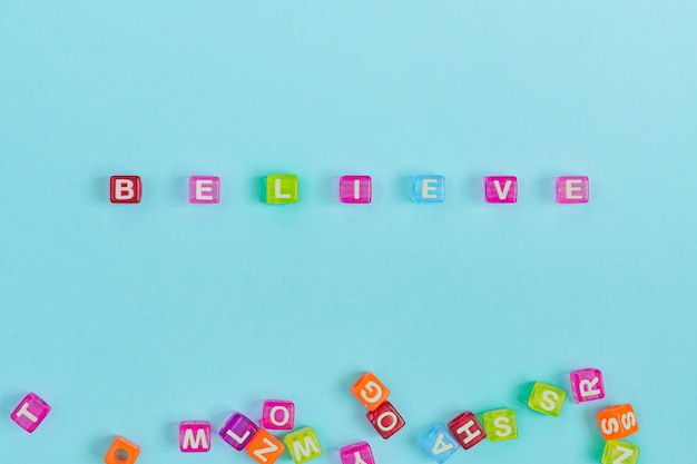 Believe inscription made of colorful cube beads with letters. festive blue background concept with copy space.