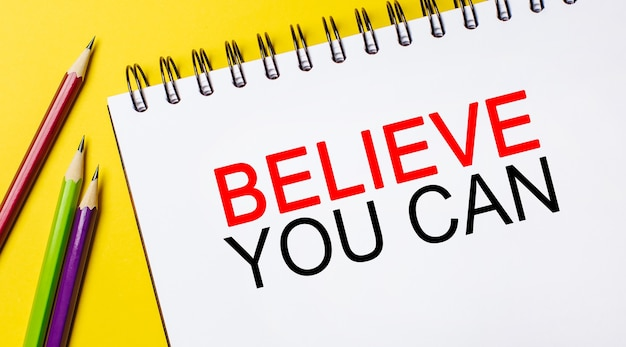 Believe you can on a white notepad with pencils on a yellow background