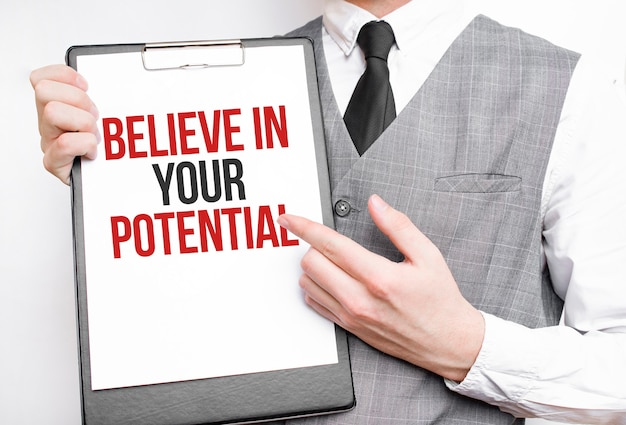 Believe in your potential inscription on a notebook in the hands of a businessman on a gray background
