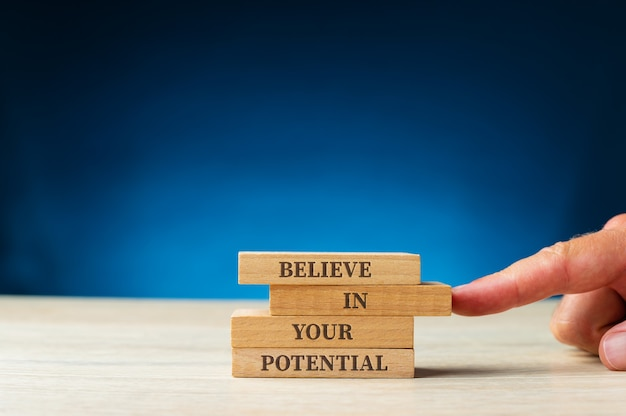 Believe in your potential sign written on wooden pegs