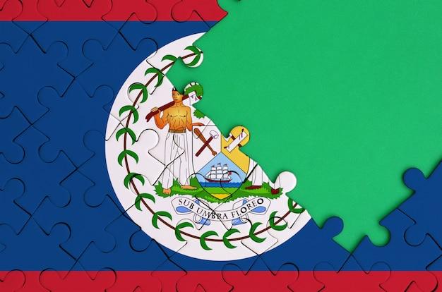 벨리즈 국기는 오른쪽에 무료 녹색 복사 공간이있는 완성 된 직소 퍼즐에 그려져 있습니다.