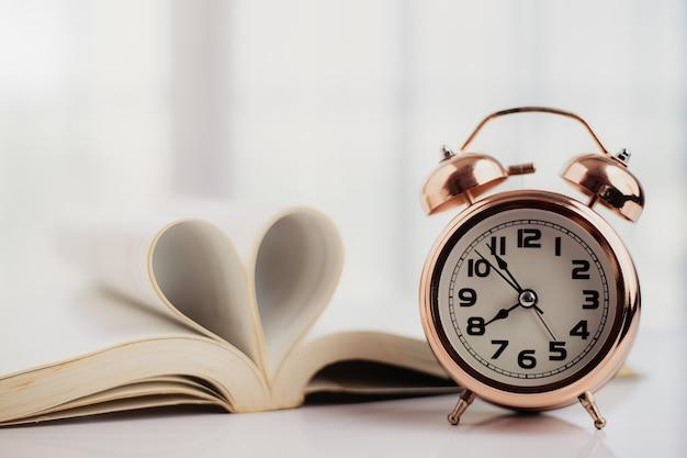 Колокольчик-будильник и открытая книга со страницей в форме сердца в таблице