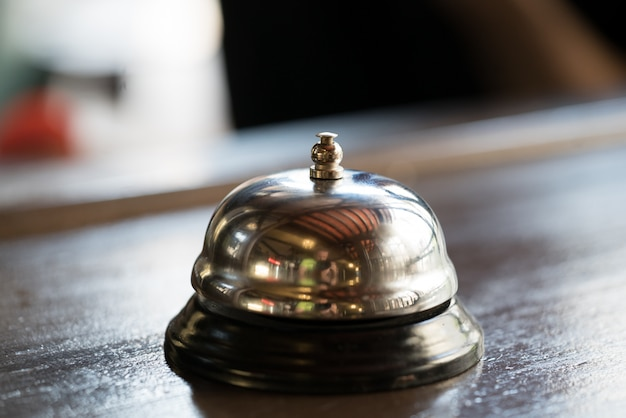 Bell for call for a waiter of a gilded color stands on wooden table in the restaurant.
