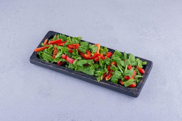 Салат из болгарского перца и салата в небольшом подносе на мраморном фоне. фото высокого качества