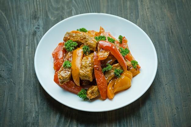 Болгарский перец и мясной салат. азиатская еда. красочный горячий салат. темный фон. место для текста.
