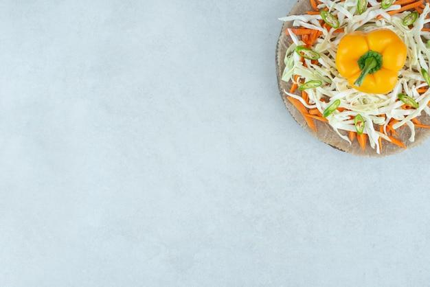 Peperone dolce e verdure tritate sul pezzo di legno.