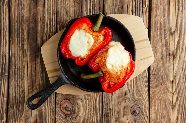 Bell pepper stuffed with meat with melted cheese mozzarella on top baked in oven in cast iron skille
