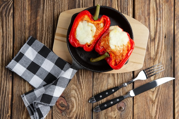 Bell pepper stuffed with meat with melted cheese mozzarella on top baked in oven in cast iron skillet