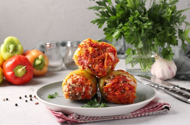 Болгарский перец, фаршированный рисом и говяжьим фаршем в томатном соусе в тарелке на светло-сером фоне, крупным планом
