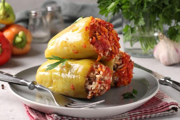 Болгарский перец, фаршированный рисом и говяжьим фаршем в томатном соусе в тарелке на светло-сером фоне