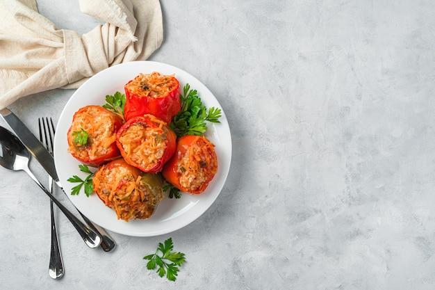 Сладкий перец, фаршированный индейкой, рисом и овощами в белой тарелке на сером фоне. здоровое, диетическое питание.