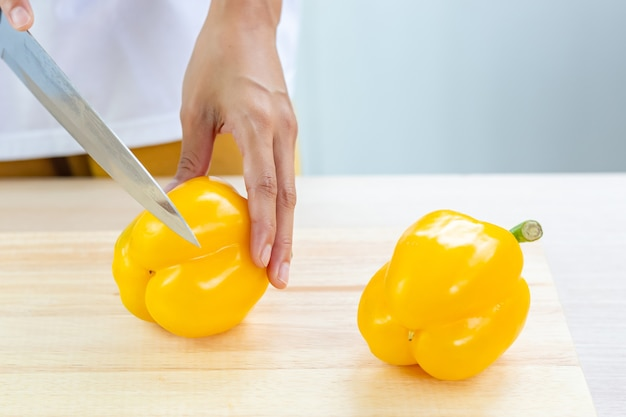 Bell pepper or sweet pepper and slices on wooden cutting board
