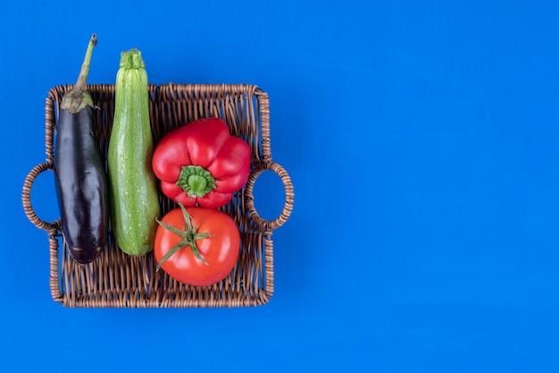Болгарский перец, помидоры, баклажаны и кабачки в деревянной корзине.
