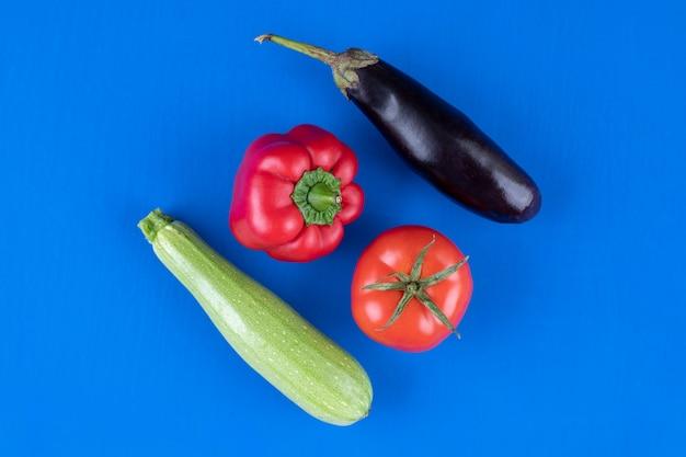 Peperone, pomodoro, melanzane e zucchine sul tavolo blu.