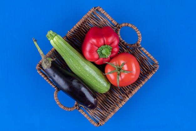 Peperone, pomodoro, melanzane e zucchine in cestino di legno