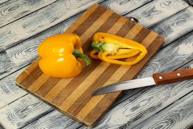 Bell pepper yellow fresh ripe and sliced on brown wooden desk and grey background
