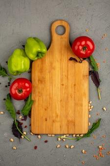 Сладкий перец вид сверху зеленых свежих спелых и красных помидоров с зеленью на сером столе