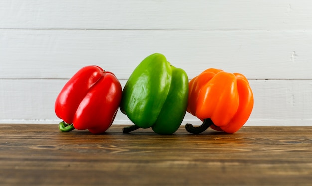 Bell peppers on dark and white wooden surface, side view.