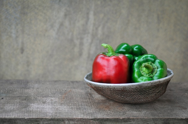 Bell peppers green and red on wooden background in retro sieve