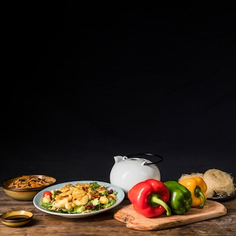 Bell peppers; teapot; soya sauce and noodles on wooden desk against black background