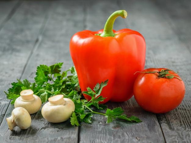 ピーマン、トマト、キノコの黒いテーブル。ベジタリアンフード。健康的な食事のコンセプトです。