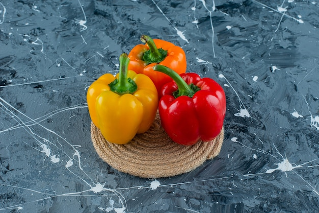 Bell peppers on a trivet, on the marble background.