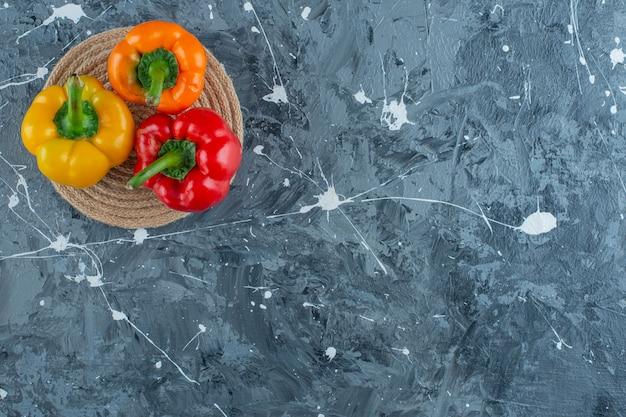 Peperoni su un sottopentola, sullo sfondo di marmo.