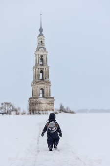 A bell tower in the middle of a frozen lake, a child walking from the back