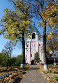 Gustynya의 가을 나무 배경에 있는 sviato-troitskyi 수도원의 종탑. 체르니히프 지역. 우크라이나. 세로 야외 촬영.